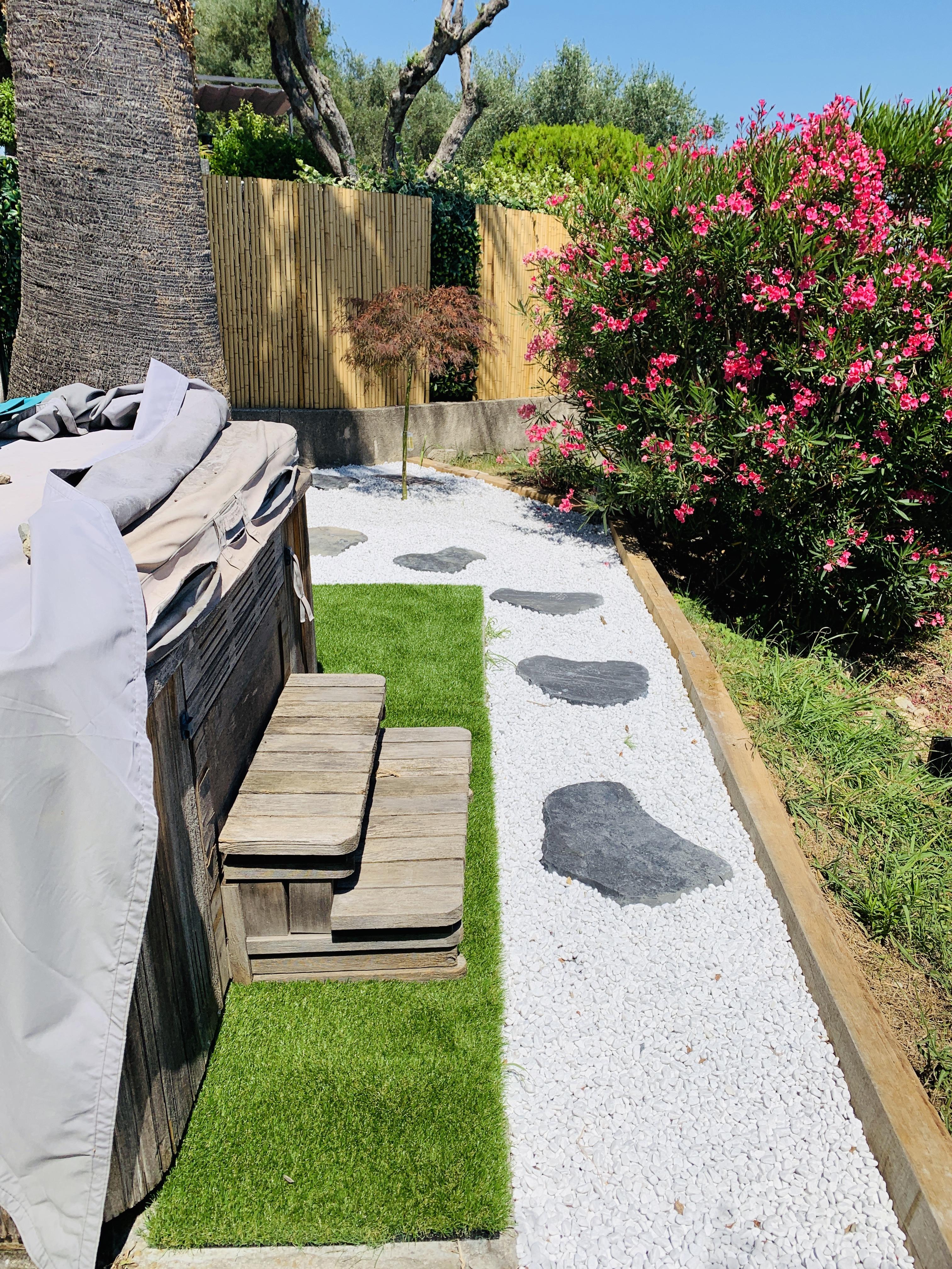 Installation d'un gazon synthétique tout autour de la dalle autour du Jacuzzi.